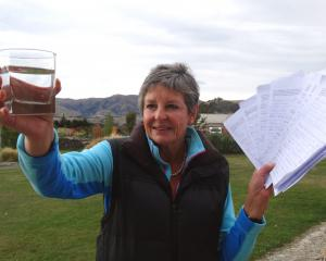 Luggate resident Cec Anderson with  a glass of the town's untreated water and a survey opposing...