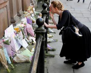 A woman blows a kiss after laying flowers for the victims of the attack, in central Manchester....