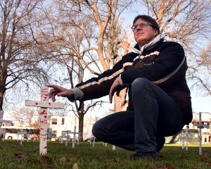 Peace and conflict studies masters student Kyle Matthews with some of the crosses at the Otago...