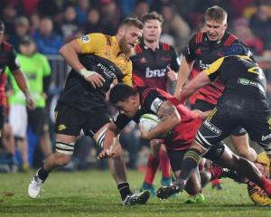 Crusaders hooker Codie Taylor is tackled in his team's match against the Hurricanes, two of the...