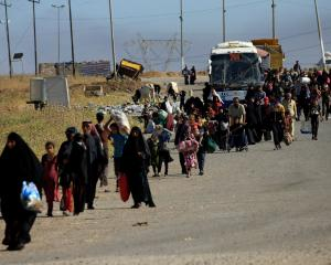 Displaced Iraqi people flee their homes during a battle between Iraqi forces and Islamic State...