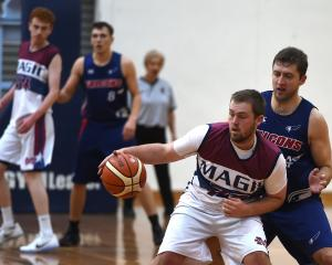 Mid City Magic Lions guard Nigel Goulstone controls the ball as Andy Bay Falcons forward Matt...
