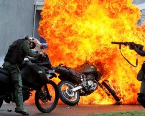 A motorcycle is set on fire during a protest against Venezuelan President Nicolas Maduro's...