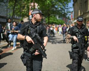 Armed police patrol as members of the public queue to lay flowers in St Ann's Square in memory of...