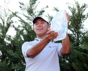 Si Woo Kim with the Players Championship trophy. Photo: Reuters