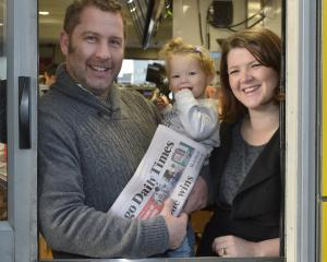 Hayden, Mavis (14 months) and Sheryl Cawte hand out a free copy of the Otago Daily Times at the...