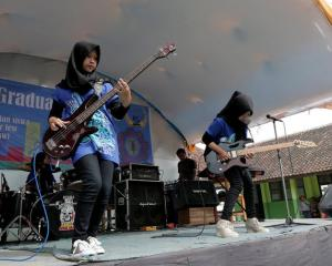 Widi Rahmawati and Firdda Kurnia, members of the metal Hijab band Voice of Baceprot, perform during a school's farewell event in Garut, Indonesia. Photo: Reuters