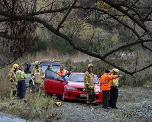 Emergency services personnel survey the scene after pulling a car out of the Arrow River...