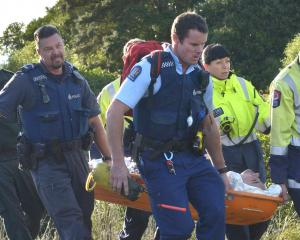 Emergency services carry a man in a Stokes basket from the Frasers Gully track yesterday, after...