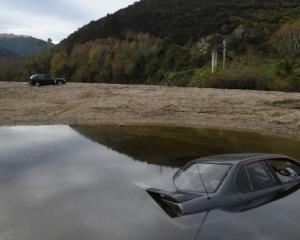 A Nissan Primera was driven into the Taieri River and a Sentra was abandoned on the riverbank at...
