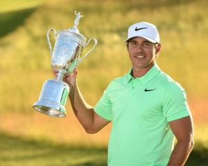 Brooks Koepka poses with the trophy after winning the US Open at Erin Hills. Photo: Rob...