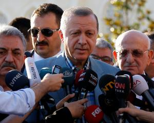 Turkey's President Tayyip Erdogan talks to media after the Eid al-Fitr prayers in Istanbul....