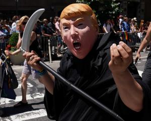 A person dressed up as US President Donald Trump in the Grim Reaper outfit participates in the...