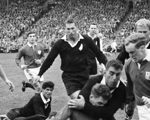 All Black Colin Meads snaffles a Lion with his brother Stan Meads in support during the last...
