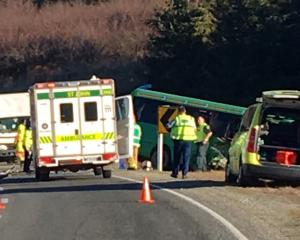 Emergency services attend a collision between a tourist bus and a truck on State Highway 8, near...