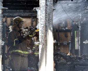 A firefighters dampens down hot spots in a charred house in Waikouaiti yesterday. Photo: Craig...