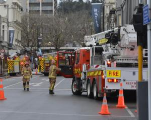 Firefighters work in a cordon in central Dunedin yesterday. Photo: Gerard O'Brien.