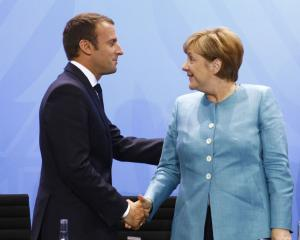 German Chancellor Angela Merkel and French President Emmanuel Macron shake hands after a Press...