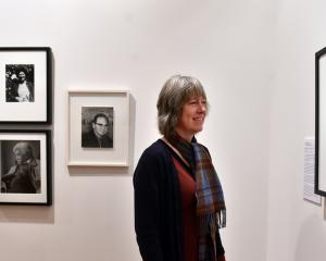 Photography curator Ann Peterson looks at one of the photographs she selected for ''Freefall''. Photo: Peter McIntosh