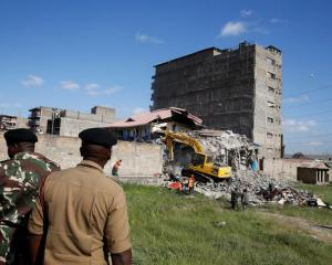 Security personnel look at the scene after a building collapsed in a residential area of Nairobi. Photo: Reuters