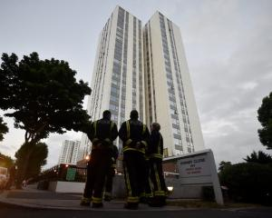 Firefighters stand outside the Burnham Tower residential block, as residents were evacuated as a precautionary measure. Photo: Reuters