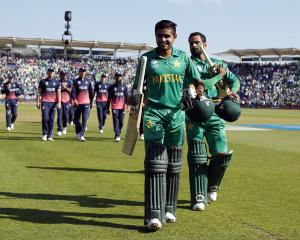 Pakistan batsmen Mohammad Hafeez and Babar Azam celebrate as they walk off after winning the...