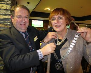 Outgoing Queenstown Rotary president Keith McIntosh hands the chains of office to Monica...