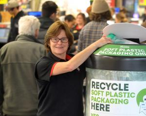 Gardens New World duty manager Debbie Lloyd places some plastic bags in a new receptacle launched...