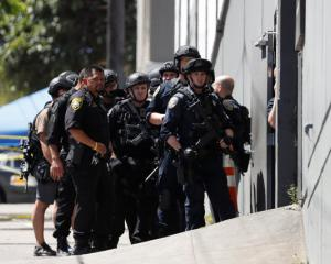 Police officers prepare to enter a UPS facility after a gunman opened fire inside the building in San Francisco. Photo: Reuters