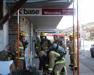 Fire fighters from the Wanaka Volunteer Fire Brigade gear up to enter the Base Backpackers. Photo...