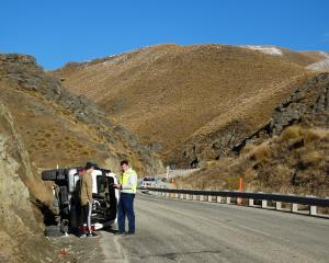 Police speak to a motorist after a one-car crash on the Crown Range Rd yesterday morning. Photo: Kerrie Waterworth