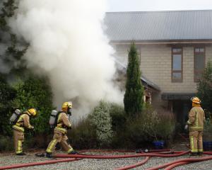 Wanaka volunteer firefighters wearing breathing apparatus attend a house fire in Dublin Bay that...