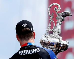 Peter Burling, Emirates Team New Zealand Helmsman holds the America's Cup after defeating Oracle...