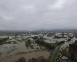 An aerial view shows water from the flooded Tokomairaro River spreading over the plains south of...
