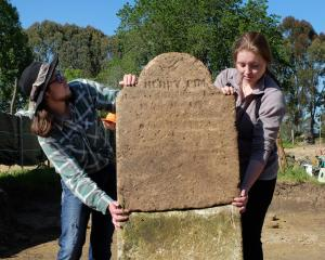 Archaeology students Teina Tutaki (left) and Alana Kelly hold up Henry Pim's headstone after it...