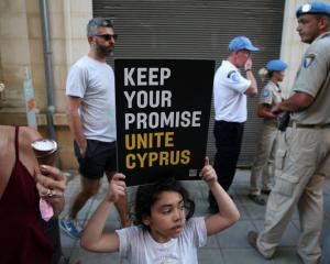 A girl holds a placard during a demonstration in favour of a peace settlement between Greek and...
