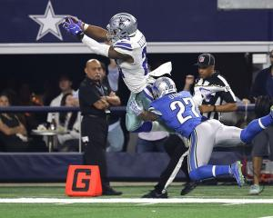 Dallas Cowboys running back Ezekiel Elliott dives for a touchdown in a game against the Detroit...