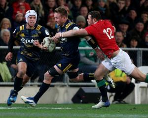 Gareth Evans slips through the tackle of Robbie Henshaw of the Lions during the Highlanders vs...
