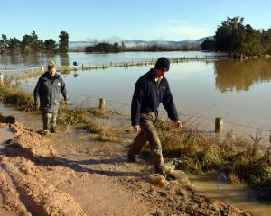 Ellie-May and Josh Adam walk through a slip covering  Henley Rd, as a flooded Taieri River runs...