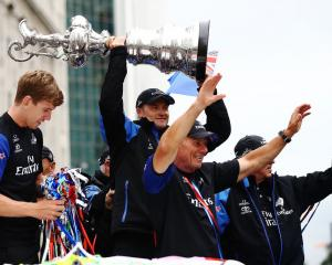 Team New Zealand members display the America's Cup during the victory parade in Auckland today....