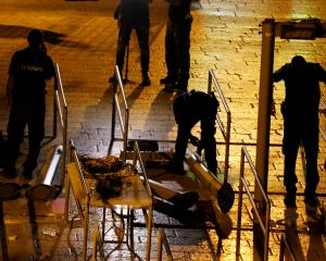 Israeli security forces remove metal detectors which were recently installed at an entrance to...