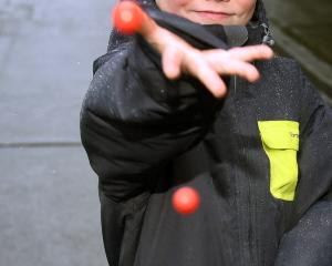 William Hanning (7), of Auckland, throws Jaffas down Baldwin St. Photo: Stephen Jaquiery.