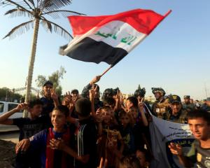 Iraqi Federal police and boys celebrate in West Mosul. Photo: Reuters