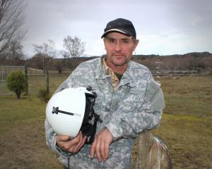 Alexandra man Robert Andrews holds the helmet of his pilot brother who died in a helicopter crash...