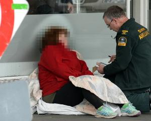 A St John staff member talks to a woman who suffered a medical event in South Dunedin yesterday...