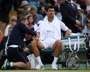 Novak Djokovic receives medical attention to his elbow prior to retiring from his quarterfinal at...