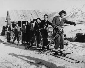 Skiers hold on to the rope tow designed and constructed by jet-boat inventor Bill Hamilton during...