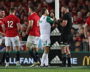Romain Poite the referee, talks to All Black captain, Kieran Read after he reverses a decision...