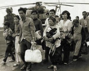 South Vietnamese refugees walk across a US Navy vessel in Saigon  as US marines load American and...