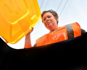 Dunedin City Council waste minimisation officer Cath Gledhill checks out a bin as part of a...